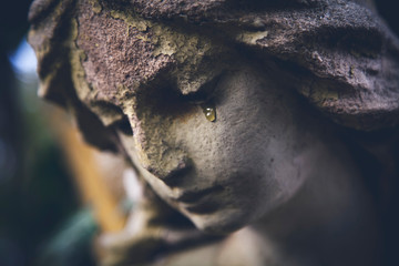Death concept. Close Up of ancient statue of crying angel with tears in face as symbol of end of human life.