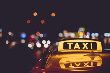 Closeup of a taxi sign on a cab during night time