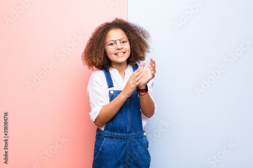Photo african american little girl feeling happy and successful, smiling and clapping