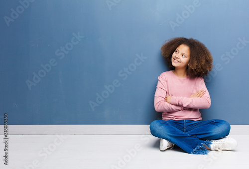 Obraz african american little girl feeling happy, proud and hopeful, wondering or thinking, looking up to copy space with crossed arms sitting on the floor - fototapety do salonu