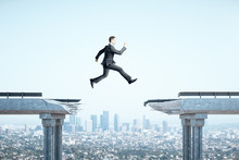 Businessman Jumping Over Gap I...