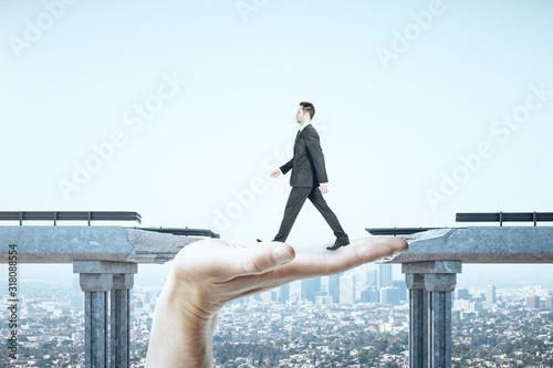 Businessman walking over gap in bridge