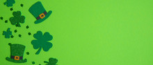 Happy St. Patrick's Day Banner Design. Top View Shamrock Leaf Clovers And Irish Elf Hats On Green Background. Saint Patricks Day Flat Lay Composition