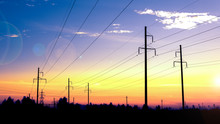 The Last Rays Of The Sun. Electricity Pylons Technology On Sunset Time Background. Electric Transmission Line, High Voltage Tower At Sunset.