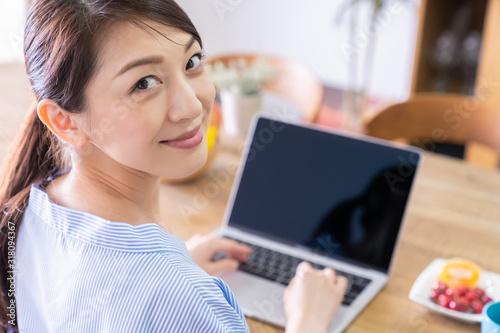 Obraz 部屋でラップトップコンピューターを見る女性 - fototapety do salonu