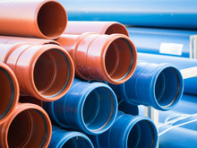 CLOSE-UP OF Stack Of Blue And Brown Plastic PIPES
