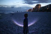 Boy Holding Flashlight While S...