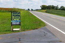 A Handmade Sign Advertising Farm Products On The Side Of A Country Road.
