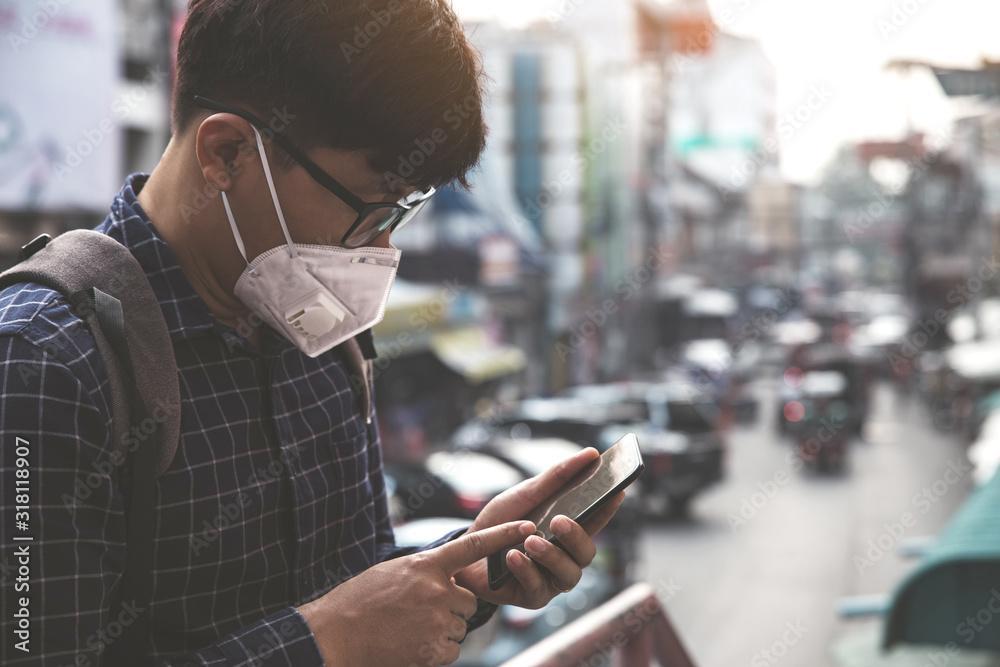 Fototapeta Concept of coronavirus quarantine. MERS-Cov, Novel coronavirus (2019-nCoV), man with medical face mask using the phone to search for news.Air pollution
