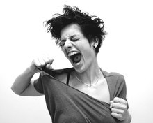 Woman Screaming While Tearing T-Shirt Against White Background