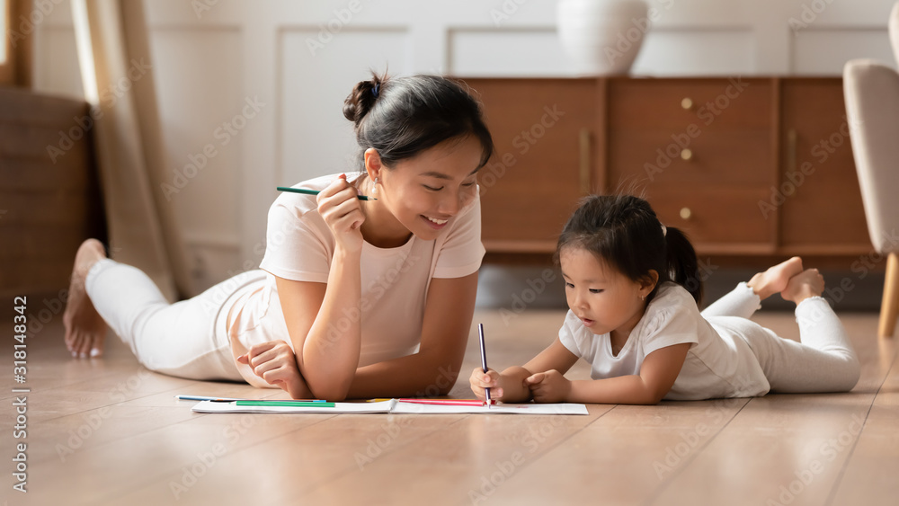 Fototapeta Young Vietnamese mom and little daughter painting at home