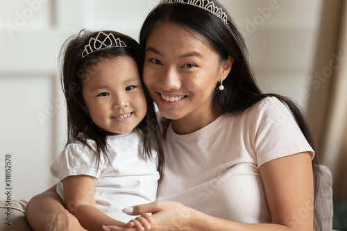 Obraz Portrait of young Asian mom and daughter posing at home - fototapety do salonu