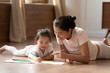 Young Asian mother and little daughter drawing together