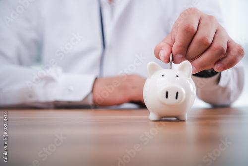 Fotografía businessman hand putting coins with piggy bank