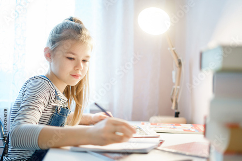 Teenage girl doing homework at table at home preparing for school test