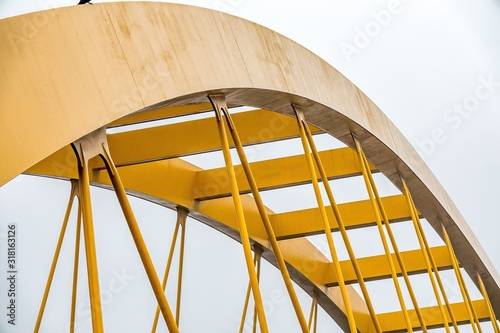 Closeup shot of the upper part of a yellow arch under a cloudy sky