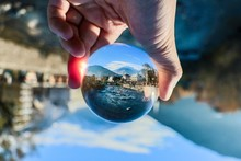 Cropped Hand Holding Crystal Ball With Reflection Of River In City