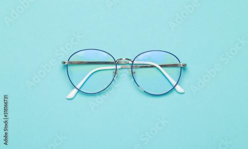 Obraz Eye glasses isolated on blue background. - fototapety do salonu