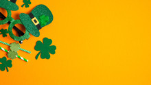 St Patricks Day Banner With Shamrock Leaf Clovers, Saint Patrick's Day Party Glasses And Drinking Straws On Orange Background. Flat Lay, Top View, Copy Space. Happy St Patrick's Day Concept
