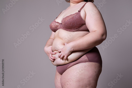 Photo Tummy tuck, flabby skin on a fat belly, plastic surgery concept