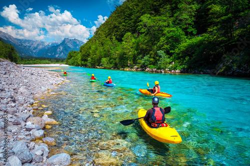 Fotografie, Obraz Sporty kayakers on the beautiful turquoise Soca river, Bovec, Slovenia