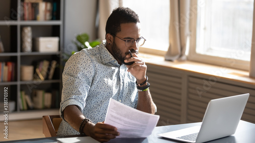 Focused african businessman holding documents looking at laptop doing research Fototapet