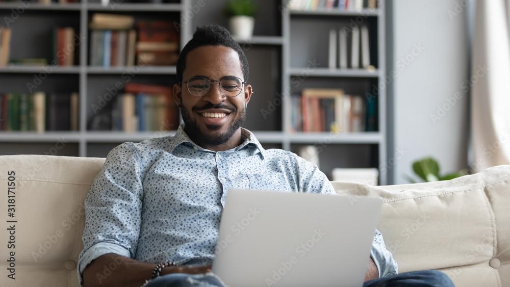 Fototapeta Smiling african man using laptop watching movies sit on sofa