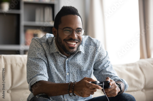 Obraz Happy young african guy holding joystick controller playing video game - fototapety do salonu