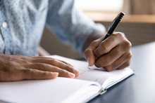 Close Up View Of African Left-handed Businessman Writing In Notebook