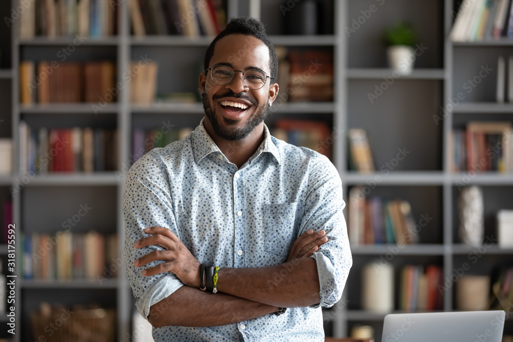Fototapeta Cheerful confident african young businessman standing at home office, portrait