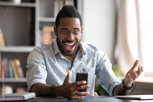 Overjoyed african business man using smartphone excited about mobile win Canvas Print