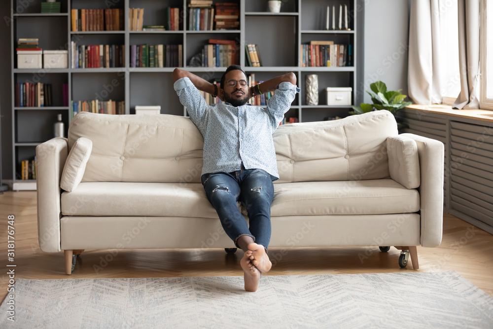 Fototapeta Serene barefoot african man resting on sofa hands behind head
