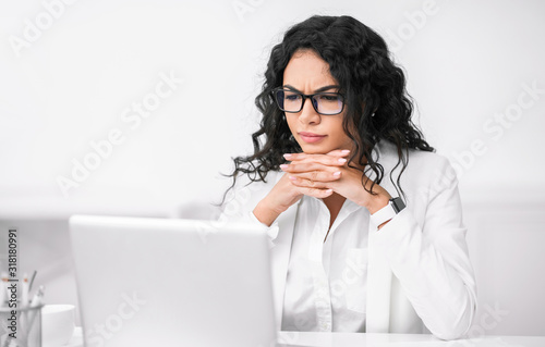 Photographie Serious hispanic manager using her personal computer