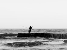 A Lone Fisherman On The Pier In A Storm.