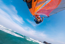 A Windsurfer With A Bright Sail And Board Does The Trick Jump In The Air Over The Tropical Sea