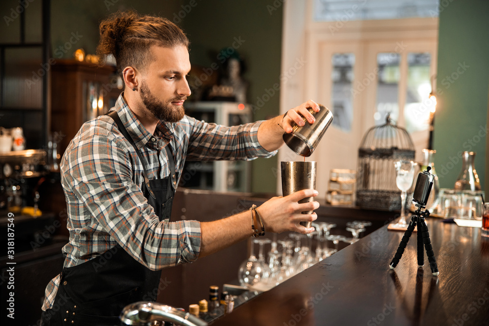 Fototapeta Bartender mixing a cocktail drink in cocktail shaker
