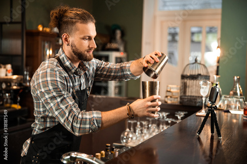 Fototapeta Bartender mixing a cocktail drink in cocktail shaker obraz