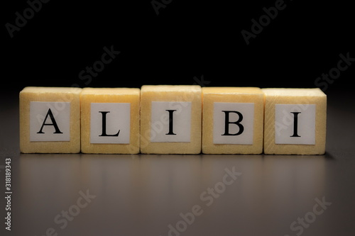 Photo The word ALIBI written on wooden cubes isolated on a black background