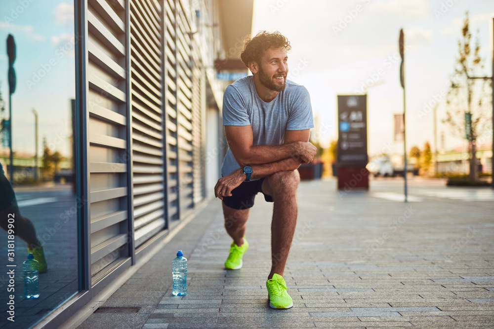 Fototapeta Young man exercising / stretching in urban area.