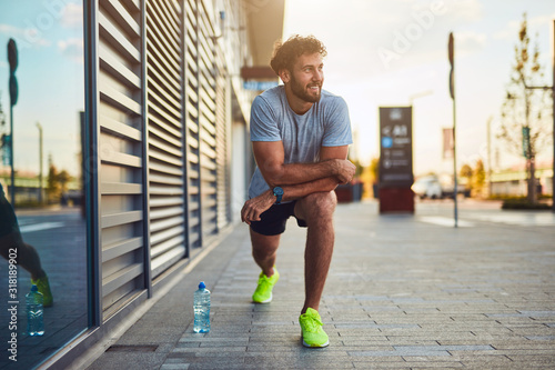 Foto Young man exercising / stretching in urban area.