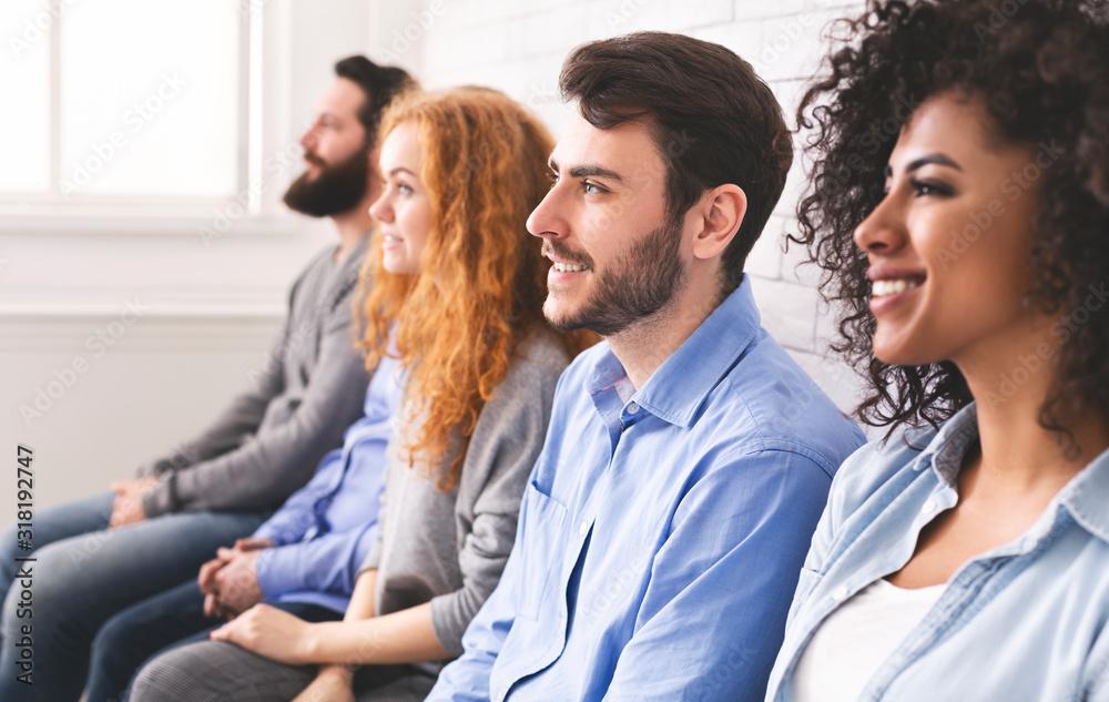Fototapeta Multiethnic millennial people sitting in row and looking at speaker