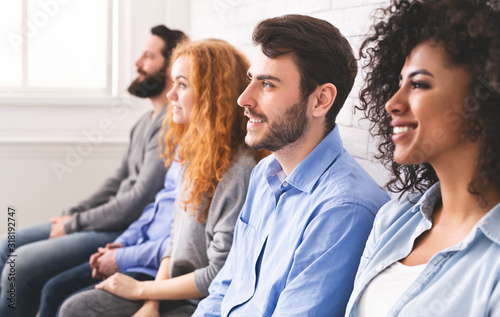 Multiethnic millennial people sitting in row and looking at speaker