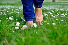 Low Section Of Woman Walking On Grassy Field
