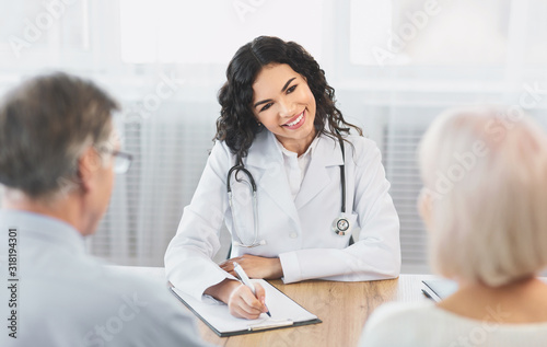 Fotografía Mexican doctor writing diagnosis consulting couple at office