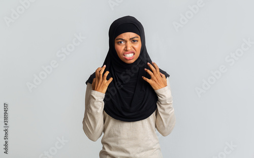 Annoyed black muslim woman emotionally gesturing with hands and grimacing Wallpaper Mural