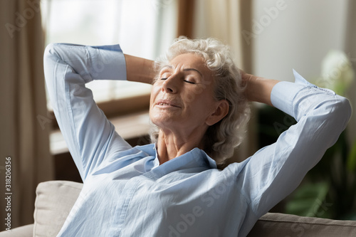 Serene mature woman relaxing on comfortable couch in living room. Canvas Print