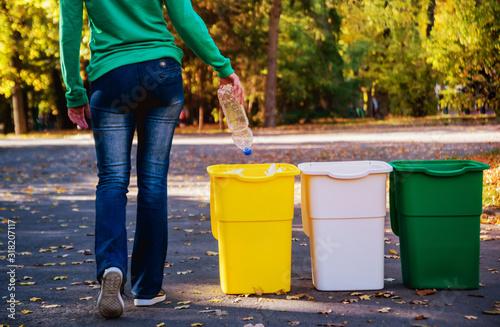 Fotografía Volunteer girl sorts garbage in the street of the park