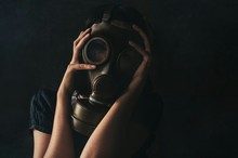 Woman Wearing Gas Mask Against Black Background
