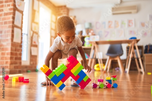 Fotografia Beautiful african american toddler playing with wooden blocks train toy around l