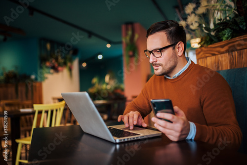 Handsome man working on laptop and using smart phone, copy space.